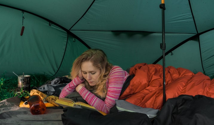 Woman reading in a tent.