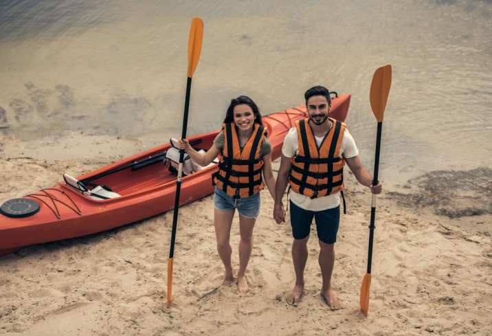 a couple with a kayak and oars