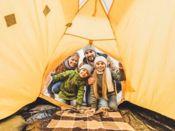 Family looking inside a clean tent.